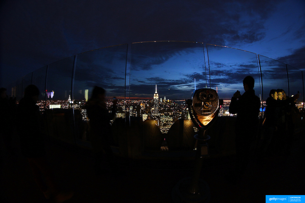A panoramic fisheye view of Manhattan, New York, at night time as tourists take pictures from the Top of the Rock, the observatory deck at Rockefeller Center showing the Empire State Building, Manhattan, New York, USA.  Photo Tim Clayton