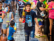 13 APRIL 2018 - BANGKOK, THAILAND:  A man walks away from a water fight on Silom Road during the first day of Songkran in Bangkok. Songkran is the traditional Thai New Year celebration best known for water fights.    PHOTO BY JACK KURTZ