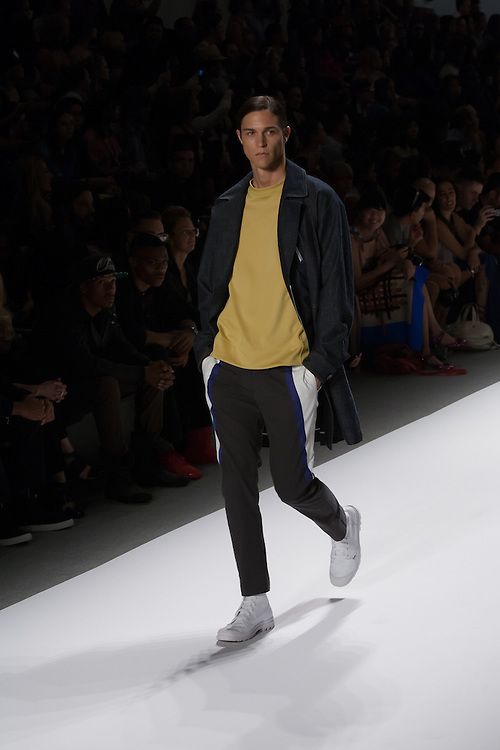 A sporty men's outfit with black and white pants, mustard top and long jacket by Richard Chai at the Spring 2013 Mercedes Benz Fashion Week show in New York.