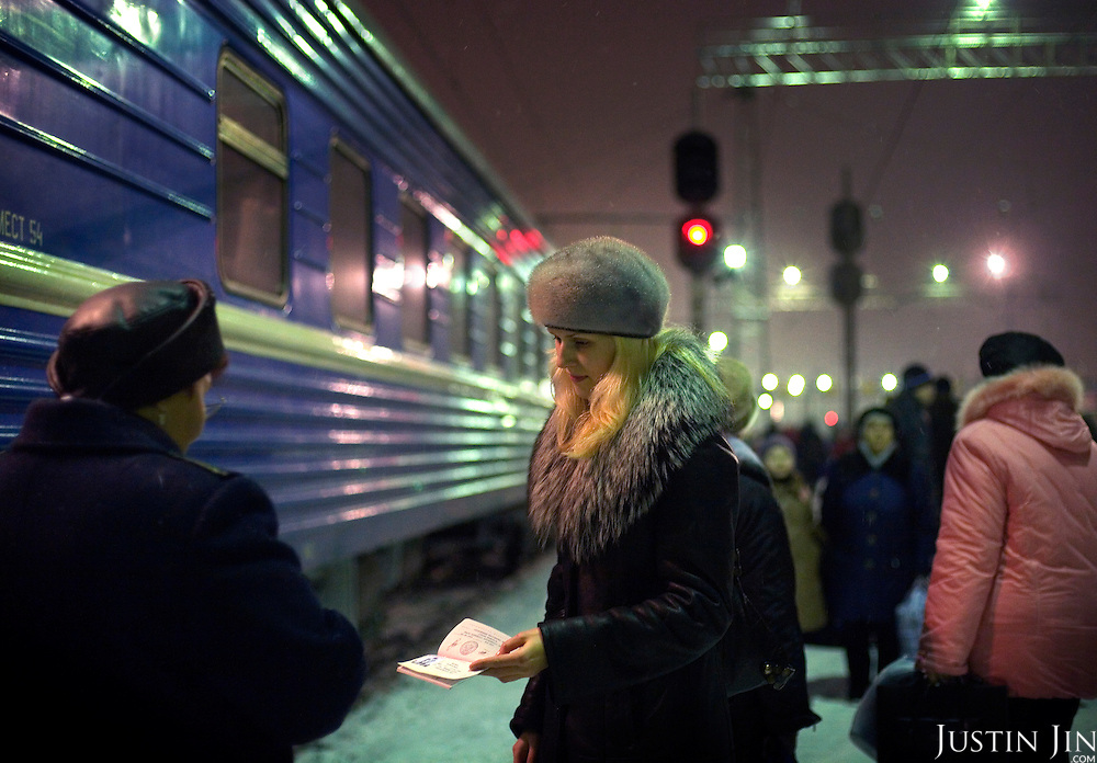 A passenger boards a night train in Perm, an industrial city in central Russia. The train, beginning in Berlin, Germany, goes through Poland and Belarus, and ends in Irkutsk, Russia. The entire journey takes six days.