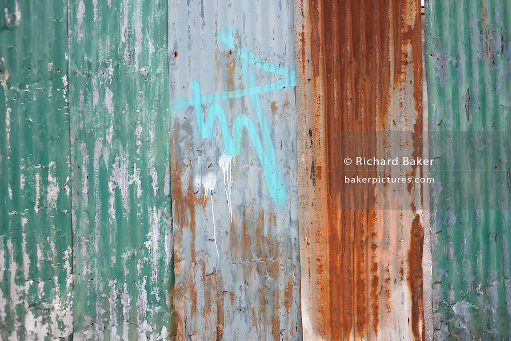 Rusting corrugated iron sheeting and sprayed graffiti on wasteland in Canning Town, Newham, East London..
