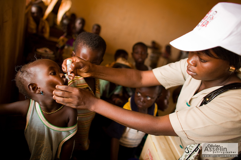 A community health nurse vaccinates children against polio at the Gbulahabila primary school in the village of Gbulahabila, northern Ghana on Wednesday March 25, 2009..
