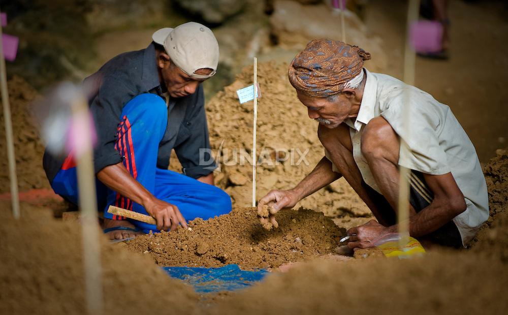 Manggarai workers sift each bucketful of sediment recovered from the Liang Bua excavations by hand. Labels on stake differientiate the source of each sediment pile.