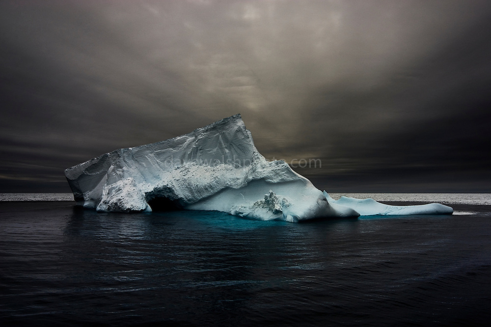"""Formerly part of a tabular ice shelf,  an iceberg slumps into the Southern Ocean. Antarctica, 2007<br /> <br /> <br /> Limited edition Giclée Prints available - contact me for more details.<br /> <br /> This mage can be licensed via Millennium Images. Contact me for more details, or email mail@milim.com For prints, contact me, or click """"add to cart"""" to some standard print options."""