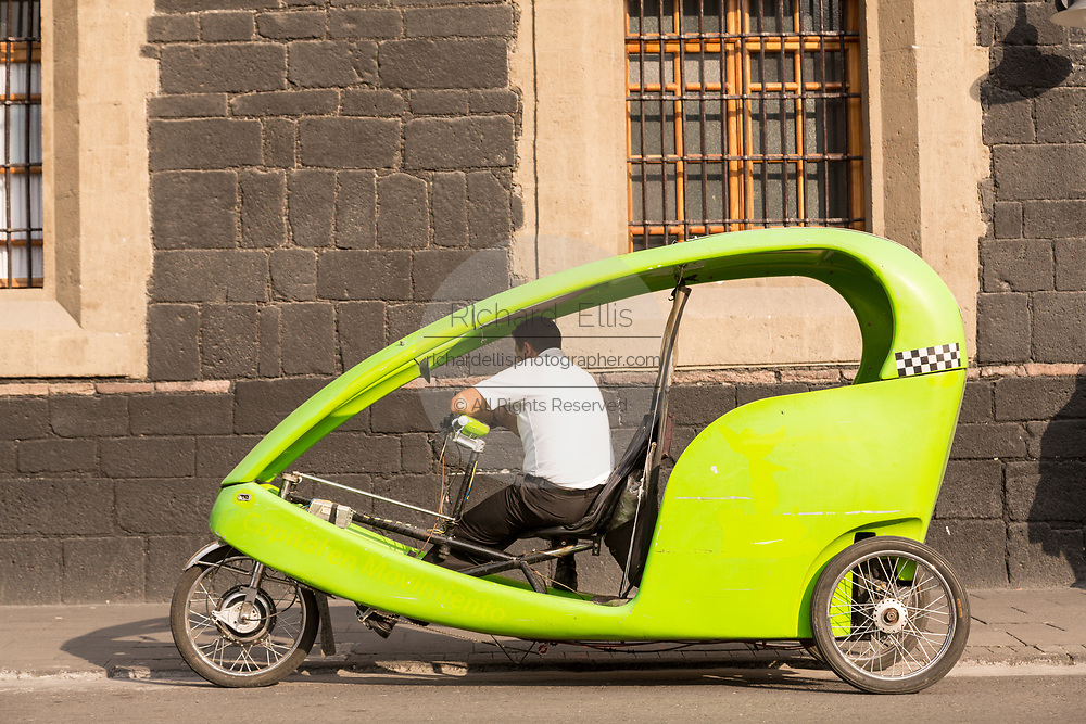 An eco pedicab waits for a customer in the Plaza Santo Domingo in the historic district of Mexico City, Mexico. The lime green cycle rickshaws are part of the Capital in Motion environmentally friendly transport initiative.