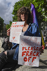 June 9, 2017 - London, UK - London, UK. A woman carries two signs, one for Jeremy Corbyn and one against Theresa May.  Anti-Tory protesters demonstrate outside Downing Street on the day that the General Election results produced a hung Parliament.  A variety of different groups, from LGBT supporters to Save the NHS supporters, gathered to make their views heard. (Credit Image: © Stephen Chung/London News Pictures via ZUMA Wire)