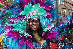 London, August 29th 2016. A woman smiles for the camera as the procession progresses along Ladbroke Grove during day two of Europe's biggest street party, the Notting Hill Carnival.