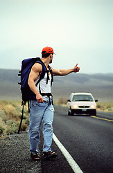 Muscular man in sleeveless tee shirt hitchhiking on a road in Death Valley, CA