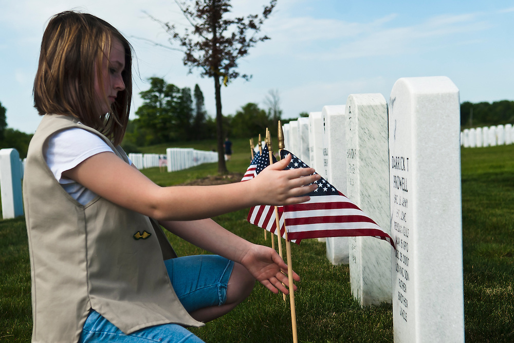 Lathan Goumas | MLive.com..Hanna Morawski, 12, of Davisburg, makes sure a miniature American flag is straight as she places it in front of a headstone for the Memorial Day weekend at the Great Lakes National Cemetery in Holly, Mich. on Friday May 25, 2012.