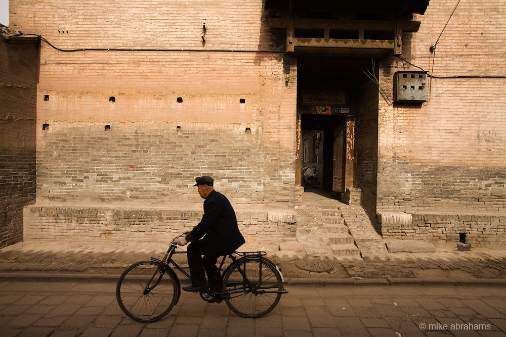 A man rides his bike down a traditional paved street in Pingyao, People's Republic of China