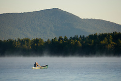 A paddler canoeing on Umbagog Lake near the Umbagog Lake State Campground in Errol, NH.  Early morning.
