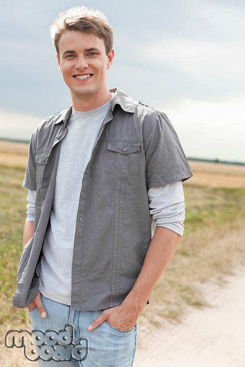 Portrait of handsome young man with hands in pockets standing on field