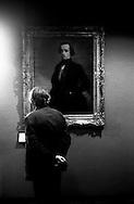 Au Louvre, un homme regarde un tableaux dans la galerie peinture française.