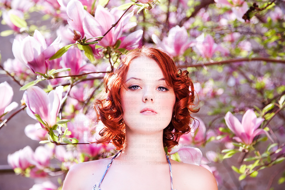 Redheaded female in front of pink magnolias looking at camera