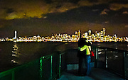 Seattle seen from a ferry in Puget Sound making a romantic mood with a hugging couple watching the lights, Seattle, WA, USA