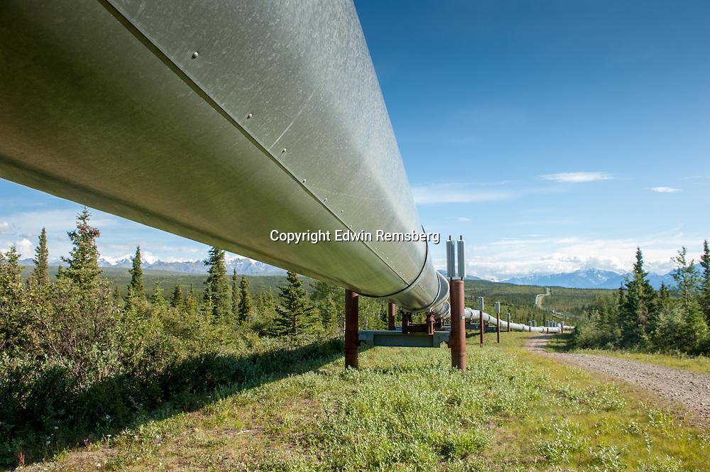 Trans-Alaska Pipeline (Alyeska pipleline) running through landscape with Mountain range in the distance in Alaska.