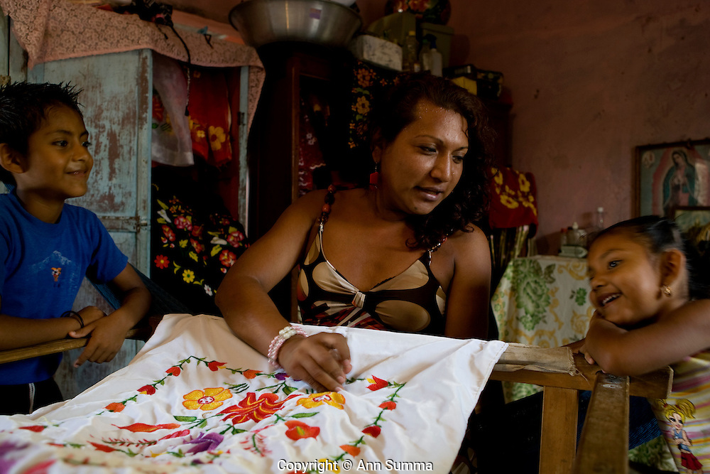 Juchitan, Mexico: Adrianna (Adan) is a seamstress and a muxe; here at home embroidering, and with mother whom she takes care of. Adrianna was beaten with a cactus by his brother when he came out as a child. She wants to be in a relationship with a man but mother makes that difficult.  Muxes are very common, and accepted, in this Southern Oaxacan region, which claims to not discriminate against gays. The matriarchal society is still driven by women but in flux in the machismo culture of Mexico. Dec. 28, 2008.(photo: Ann Summa).