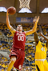 Feb 20, 2016; Morgantown, WV, USA; Oklahoma Sooners forward Ryan Spangler (00) shoots and is defended by West Virginia Mountaineers forward Devin Williams (41) during the first half at the WVU Coliseum. Mandatory Credit: Ben Queen-USA TODAY Sports