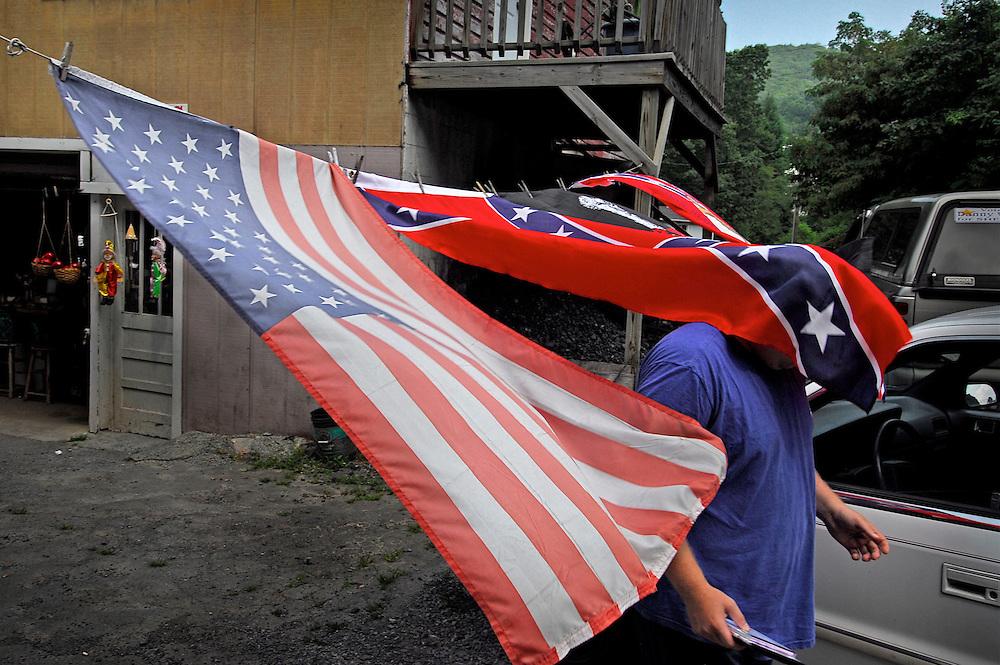 Man walks through a confederate flag in West Virginia.