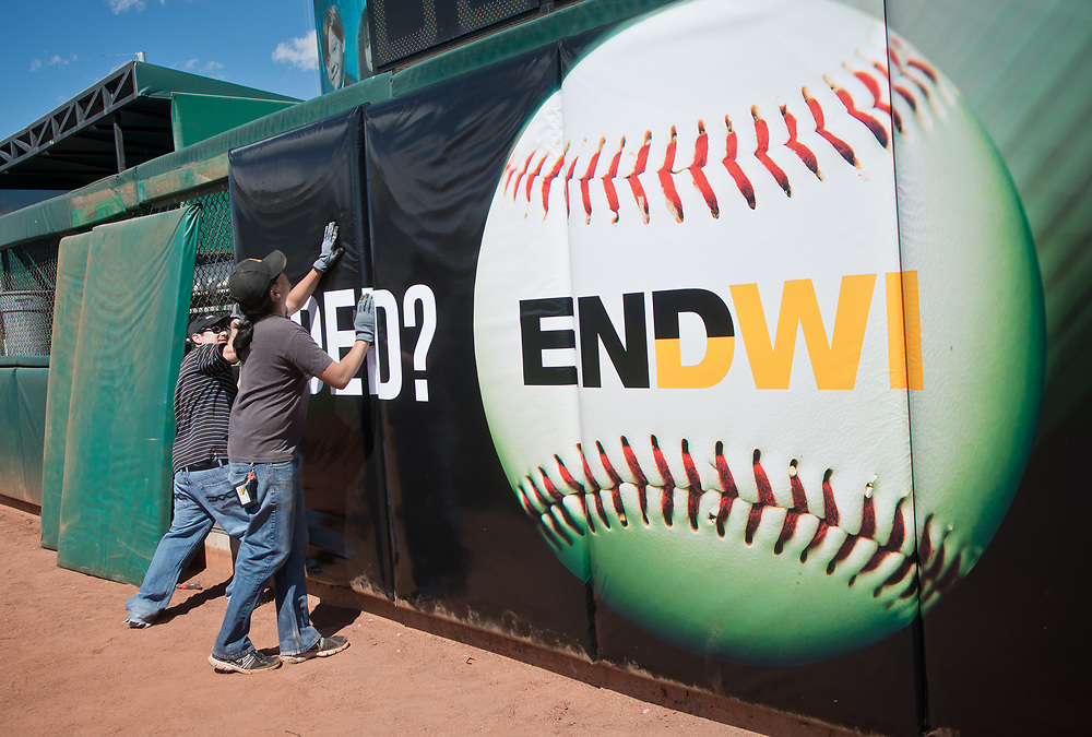 mkb032317/metro/Marla Brose --  From left, Greg Padilla and Joaquin Montoya, from The Sign Store, install new signs on the outfield wall in preparation of opening day, which is about two weeks away. (Marla Brose/Albuquerque Journal)