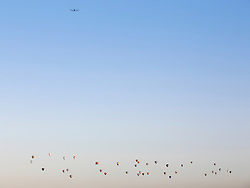 © Licensed to London News Pictures. 07/06/2015. London, UK. A plane passes as hot air balloons rise over the London skyline on a summer morning. 50 Balloons took to the skies as part of the Lord Mayor's Regatta to raise money for charity. the last mass ascent balloon flight over London was over 20 years ago.Photo credit : Stu Mayhew/LNP
