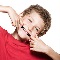 little caucasian boy portrait  grimacing mischief isolated studio on white background
