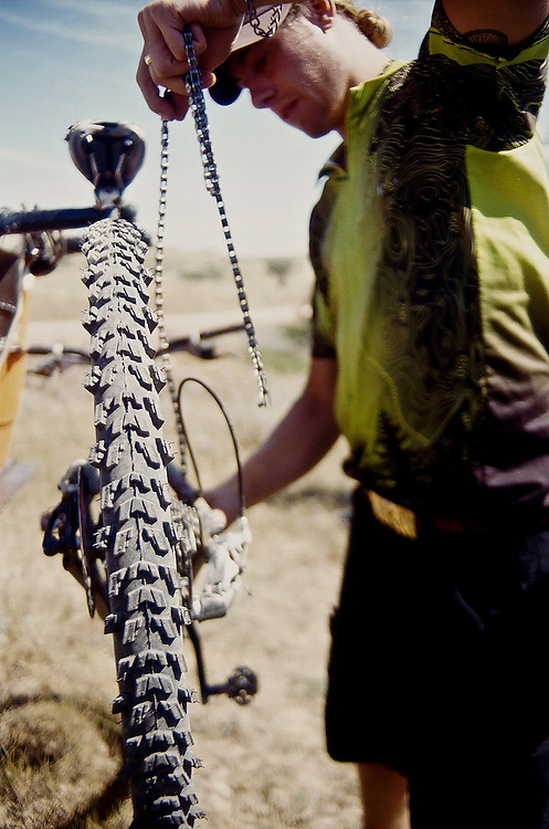Escape Adventures guide Tom Morlock repairs a customers bike on the Maah Daah Hey trail, North Dakota.