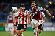 Luke O'Nien of Sunderland  and Ben Gibson of Burnley   chase a through ball during the EFL Cup match between Burnley and Sunderland at Turf Moor, Burnley, England on 28 August 2019.