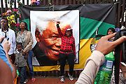 Well wishers pose to have their photos taken next to a portrait of Madiba. Crowds gather to mourn the death and celebrate the life of Nelson Rolihlahla Mandela outside his former home in Vilakazi street in Soweto. Johannesburg. South Africa<br />