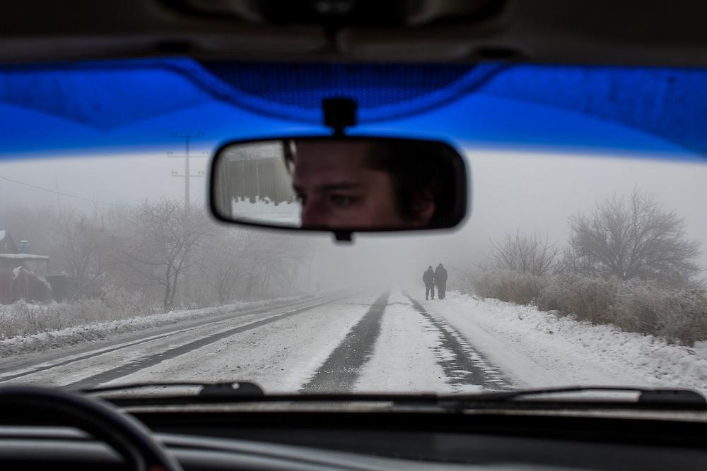 SNIZHNE, UKRAINE - DECEMBER 8, 2014: Pedestrians are seen through the fog along the road between Donetsk and Luhansk in Snizhne, Ukraine. CREDIT: Brendan Hoffman for The New York Times
