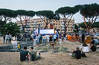 """ROME, ITALY - 27 JUNE 2017: The audience waits for the premiere of """"Don Giovanni OperaCamion"""", an open-air opera performed on a truck in San Basilio, a suburb in Rome, Italy, on June 27th 2017.<br /> <br /> Director Fabio Cherstich's idae of an """"opera truck"""" was conceived as a way of bringing the musical theatre to a new, mixed, non elitist public, and have it perceived as a moment of cultural sharing, intelligent entertainment and no longer as an inaccessible and costly event. The truck becomes a stage that goes from square to square with its orchestra and its company of singers in Rome. <br /> <br /> """"Don Giovanni Opera Camion"""", after """"Don Giovanni"""" by Wolfgang Amadeus Mozart is a new production by the Teatro dell'Opera di Roma, conceived and directed by Fabio Cherstich. Set, videos and costumes by Gianluigi Toccafondo. The Youth Orchestra of the Teatro dell'Opera di Roma is conducted by Carlo Donadio."""