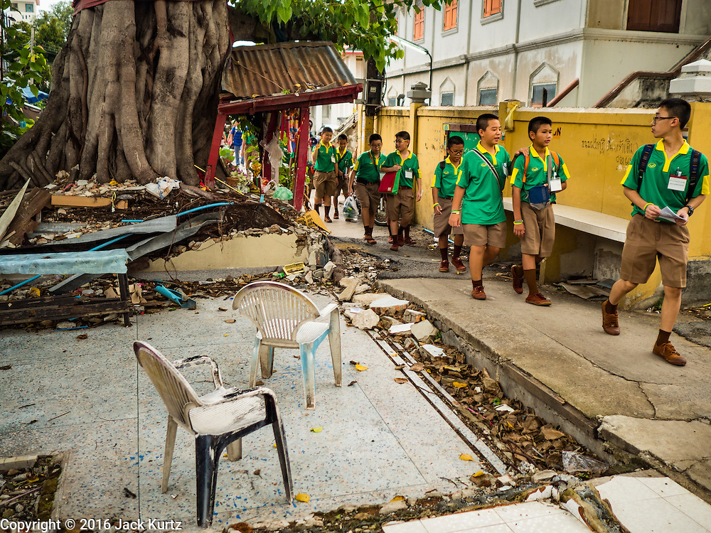 20 SEPTEMBER 2016 - BANGKOK, THAILAND:  Thai students walk past what used to be a home on the grounds of Wat Kalayanamit. One year after 54 families were forcibly evicted the grounds around Wat Kalayanamit are still undeveloped. Fifty-four homes around Wat Kalayanamit, a historic Buddhist temple on the Chao Phraya River in the Thonburi section of Bangkok, were razed and the residents evicted to make way for new development at the temple. The abbot of the temple said he evicted the residents, who lived on the temple grounds for generations, because their homes were unsafe and because he wants to improve the temple grounds. The evictions are a part of a Bangkok trend, especially along the Chao Phraya River and BTS light rail lines. Low income people are being evicted from their long time homes to make way for urban renewal.           PHOTO BY JACK KURTZ