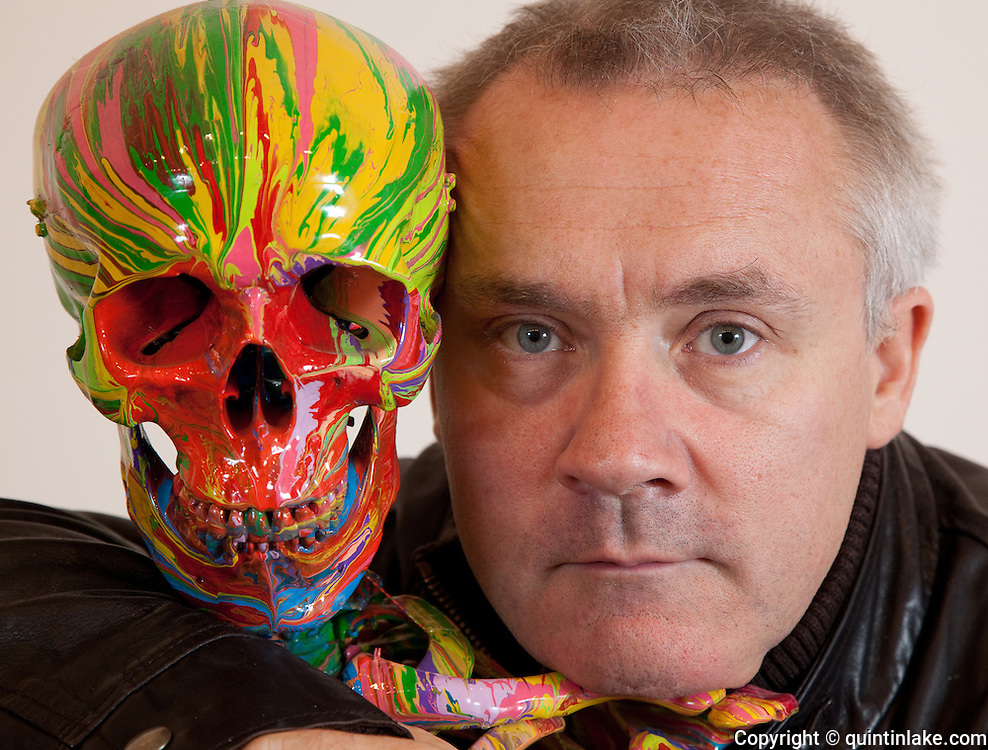 """Close-up Damien Hirst Portrait with his artwork.""""St Elmo's Fire"""".2008.Household gloss on plastic skeleton.1700 x 425 x 435 mm.© Damien Hirst. All rights reserved, DACS 2010.Photographed in his Chalford Studio, near Stroud, Gloucestershire"""