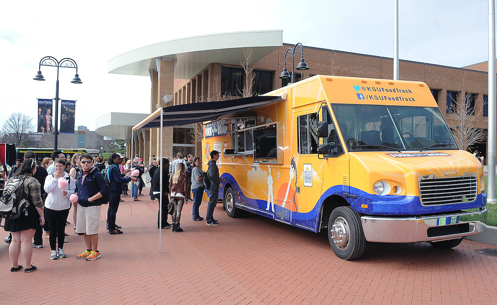 Students line up to get some dinner from the Fork in The Road food truck which is parked in front of the student center.