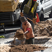 African American blue collar workers digging up the street for replacement new water pipes.