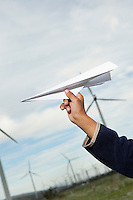 Boys hand throwing paper plane at wind farm, close-up