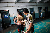 A prison gaurd pinches an inmate's flabby stomach at Klong Prem prison in Bangkok, Thailand.