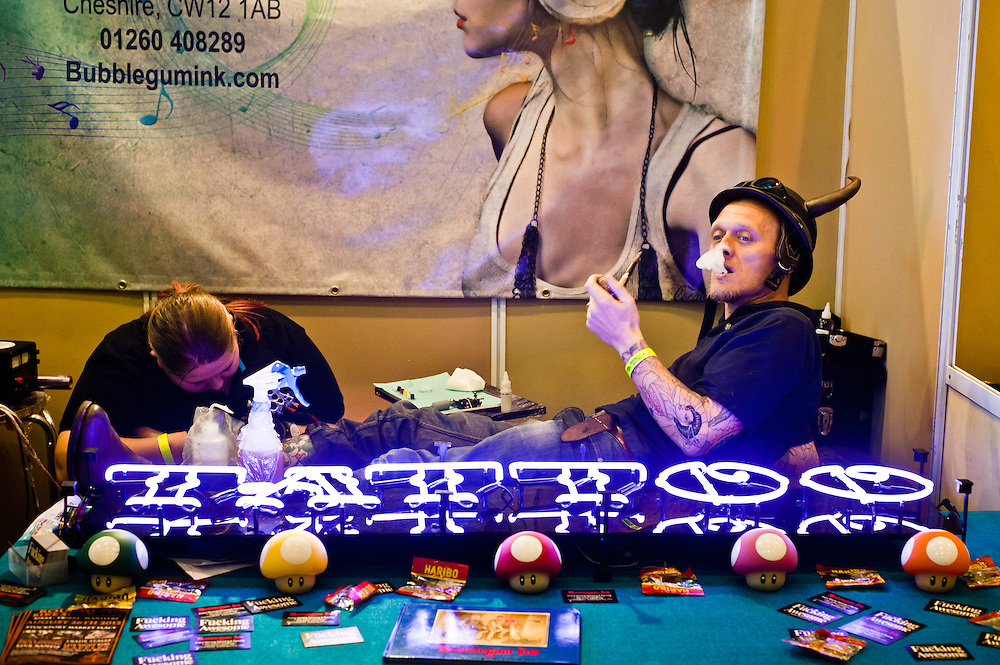 Manchester, UK - 5 August 2012: an artist creates a new tattoo on a visitor smoking a pipe during the Manchester Tattoo Show, one of the most popular conventions of the UK tattoo community.