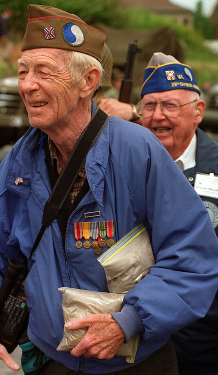 On June 3, 1994, a veteran of the US Armies 29th Infantry Division, carries bags of sand taken from Omaha Beach, Normandy, France on the 50th Anniv. of D-Day.
