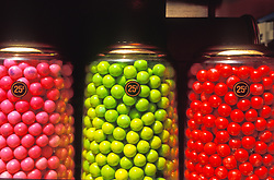 Snack  Glass jar vending machine of large jaw breaker candy gum ball assortment, children, red and green.