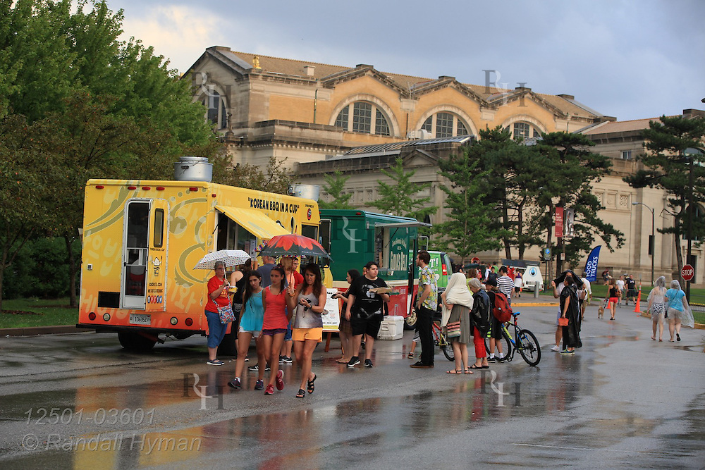 Food trucks line up in parking lot for patrons attending St. Louis Art Museum's free Outdoor Film Series on Friday nights throughout July; St. Louis, MO