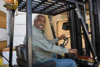 Senior man driving forklift truck