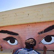 """Daniel Brewer, a muralist with Arbuckle Signs of Kansas City, Mo., paints the eyes of movie actress Audrey Hepburn from her movie """"Breakfast at Tiffany's"""" on a brick inlay atop the Optical Innovations shop at 107 W. 63rd Street in Kansas City. Brewer will also paint another mural on the west side of the building."""