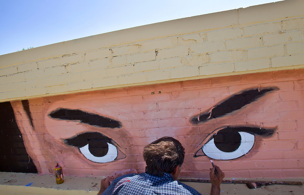 "Daniel Brewer, a muralist with Arbuckle Signs of Kansas City, Mo., paints the eyes of movie actress Audrey Hepburn from her movie ""Breakfast at Tiffany's"" on a brick inlay atop the Optical Innovations shop at 107 W. 63rd Street in Kansas City. Brewer will also paint another mural on the west side of the building."