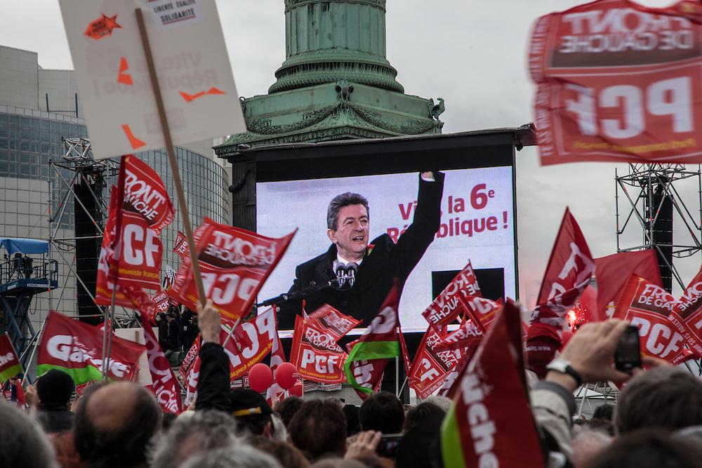Jean-Luc Mélenchon apparait sur les écrans de la place de la Bastille derrière une nuée de drapeaux, lors de la manifestation du Front de Gauche, le 18 mars 2012 à Paris.