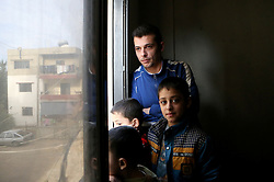 Syrian refugee Bassam Al Rahal, 30, with his sons (left to right) Ammar (5), Omar (9) and Baker (10). The family, which also includes Bassam's wife and daughter, live in an apartment in Tripoli, Lebanon, after fleeing their home in Homs, Syria.