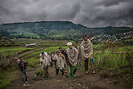 A jovial group of men return to their village by the most common mode of transportation between town and village in the Ethiopian Highlands, on foot.  Life is simple and hard in the highland.  The food supply relies largely on the rains.  The Northern Ethiopians Highlands, like most of the country, have emerged from the worse drought in decades.  In the highlands, however, the rains have returned heavier than usual, threatening the crops with too much water.