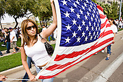 10 APRIL 2006 - PHOENIX, AZ: Women carry an American flag through Phoenix, AZ. More than 200,000 people participated in a march for immigrants's rights in Phoenix Monday. The march was a part of a national day of action on behalf of undocumented immigrants. There were more than 100 such demonstrations across the US Monday. Protestors were encouraged to wear white, to symbolize peace, and wave American flags, to demonstrate their patriotism to the US.  Photo by Jack Kurtz
