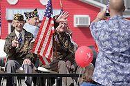 Middletown, NY  - Veterans wave to the crowd as a man, at right, takes a photograph with a digital camera during a Memorial Day  parade on May 25, 2009.