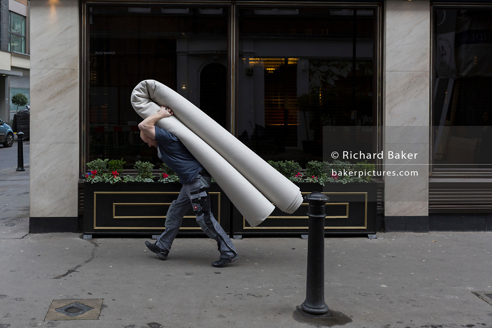 A man carries a heavy new rolled-up carpet on his back to a West End Hotel, on 6th February 2019, in London England.